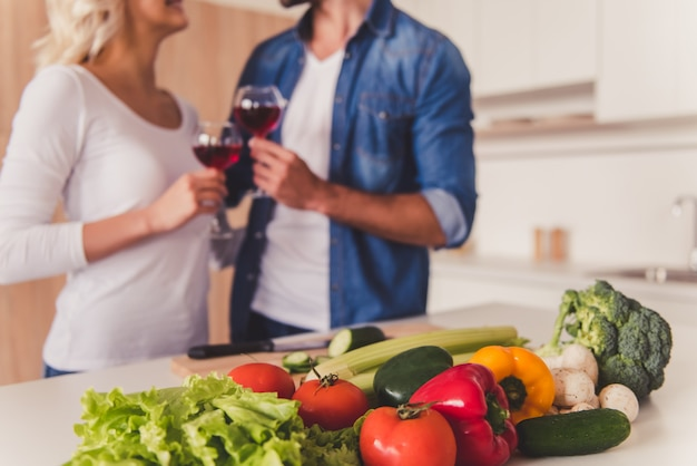 Beautiful couple drinking wine while cooking in kitchen. Premium Photo