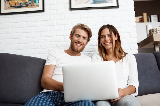 Beautiful couple holding laptop smiling   home. Free Photo