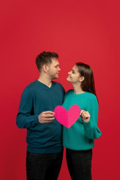 赤いスタジオの壁にピンクのハートを保持している愛の美しいカップル 無料写真