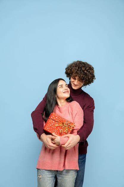 Красивая влюбленная пара на синей стене студии Бесплатные Фотографии