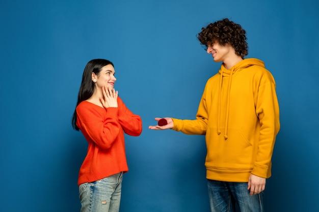 青いスタジオの壁に恋をしている美しいカップル 無料写真
