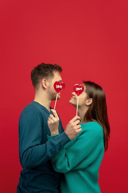 赤いスタジオの壁にロリポップを愛する美しいカップル 無料写真