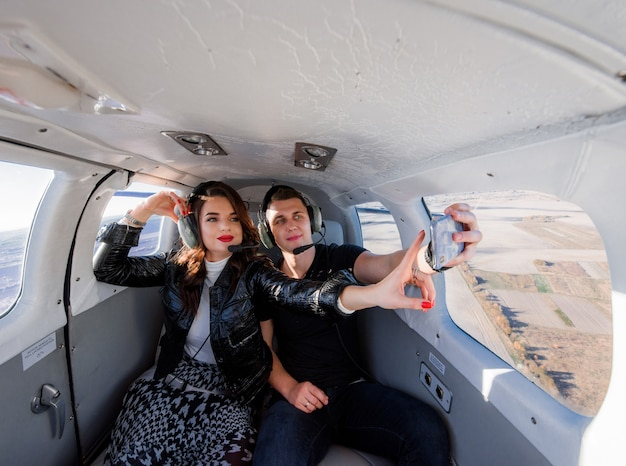 Beautiful couple is making selfie inside of helicopter with breathtaking scenery out of window Free Photo