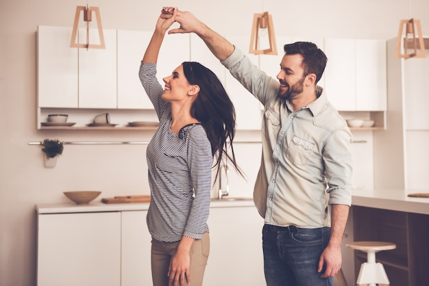 Beautiful couple is smiling while dancing in kitchen at home Premium Photo