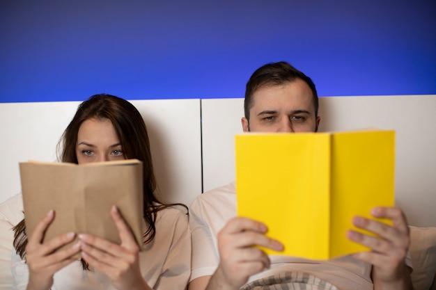 美しいカップルは開いた本の後ろに隠れている手で紙の本をベッドで産む Premium写真