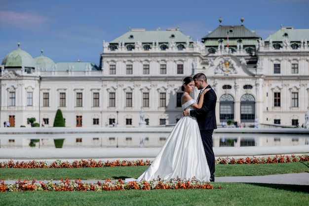 Beautiful couple in love dressed in the wedding attires in front of palace on the beautiful sunny day, wedding trip Free Photo