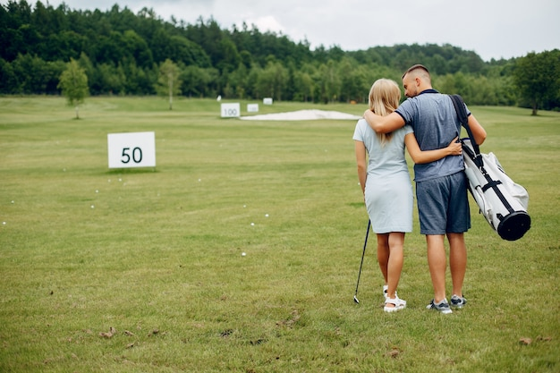 Beautiful couple playing golf on a golf course Free Photo