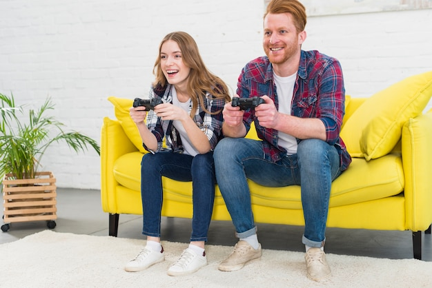 Beautiful couple playing video games on console having fun Free Photo