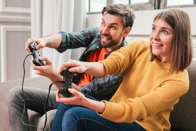 Beautiful couple playing video games on console Free Photo