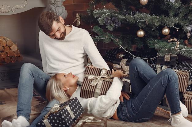 クリスマスツリーの近くに家に座っている美しいカップル 無料写真
