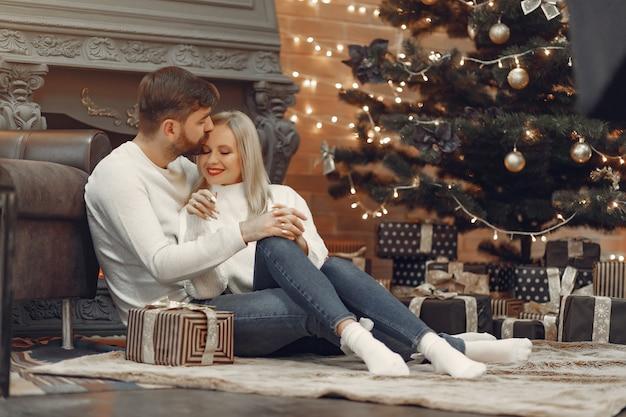 Belle coppie che si siedono a casa vicino all'albero di natale Foto Gratuite