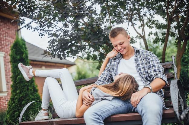 Красивая пара, сидя на скамейке. улыбающийся мужчина и женщина смотрят друг на друга. девушка ложится на скамейку и кладет голову на ноги парня. Premium Фотографии