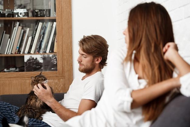 自宅のソファーに座っている美しいカップル。猫をなでる男。 無料写真