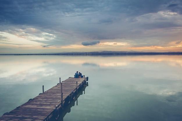 Beautiful couple sitting on a wooden dock under a beautiful sunset sky Free Photo