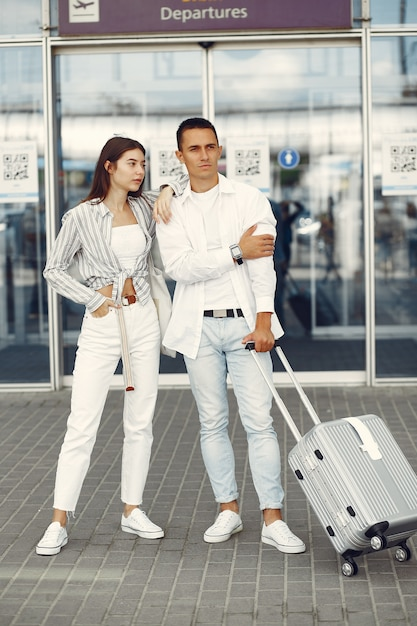Beautiful couple standing near the airport Free Photo