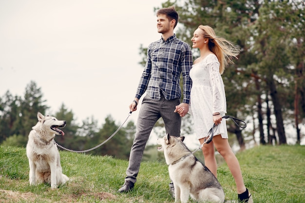 Beautiful couple in a summer forest with a dogs Free Photo