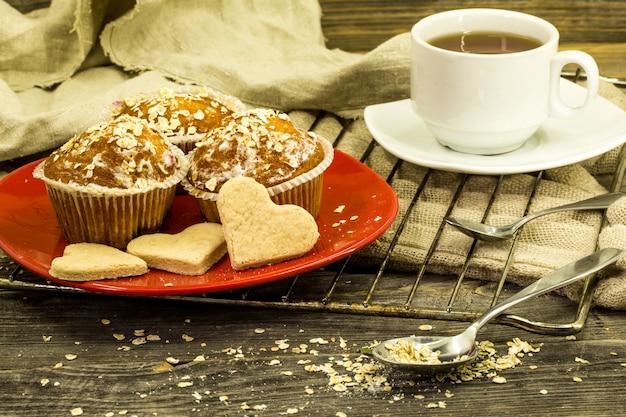 Красивые кексы с ягодами на деревянный стол в красной тарелке Бесплатные Фотографии