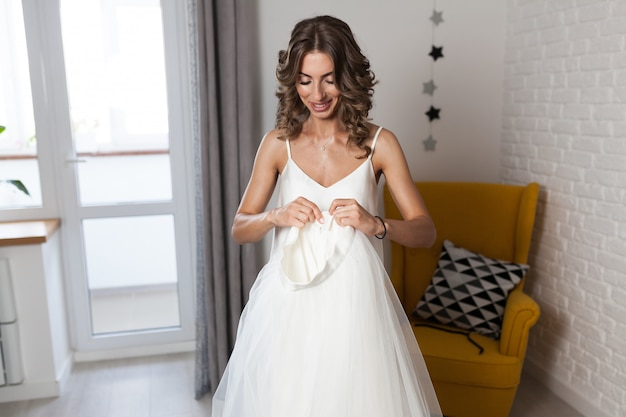 A beautiful curly-haired girl, a future bride measuring a wedding dress in her house before the wedding. Premium Photo
