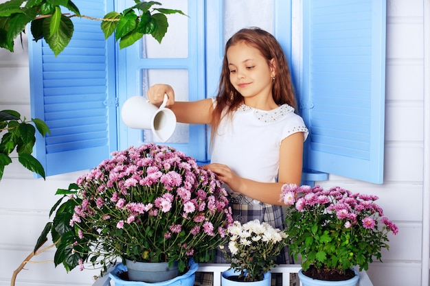 Beautiful curly little girl watering flowers. Premium Photo
