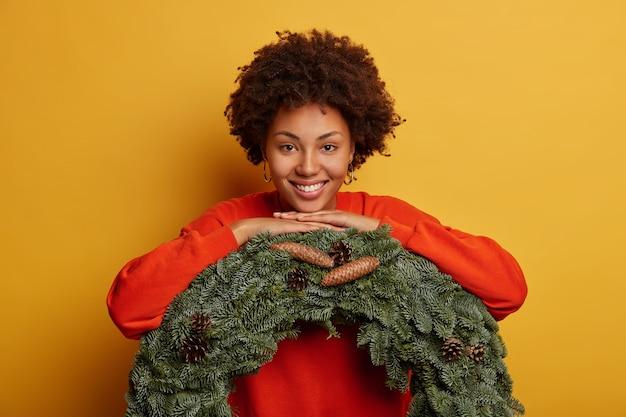 美しい巻き毛の女性は、緑の花輪に寄りかかって、カジュアルなジャンパーを着て、クリスマス前に家を飾り、歯を見せる笑顔を持ち、黄色の背景の上に孤立しています。 無料写真