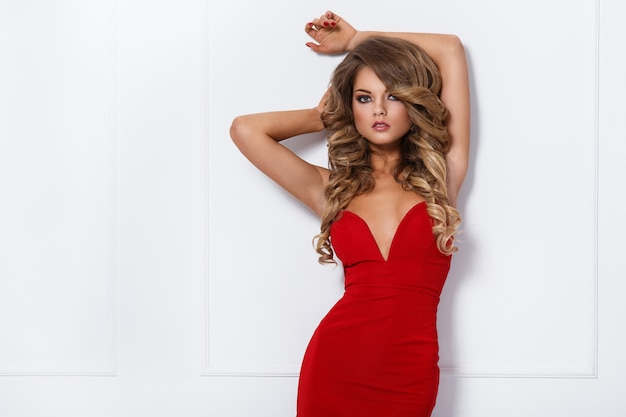 Beautiful curly woman in red dress Free Photo