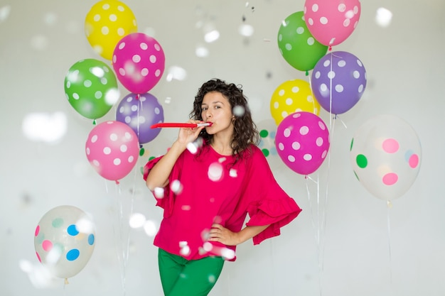 Beautiful cute cheerful girl with colored balloons laughs and throws confetti Premium Photo