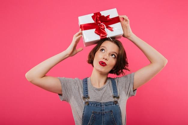 Beautiful cute young woman holding gift box. Free Photo