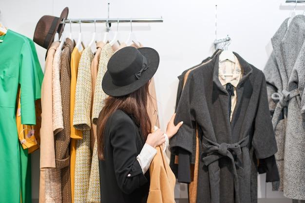 쇼핑몰에서 의류 쇼핑 아름 다운 검은 머리 여자 프리미엄 사진