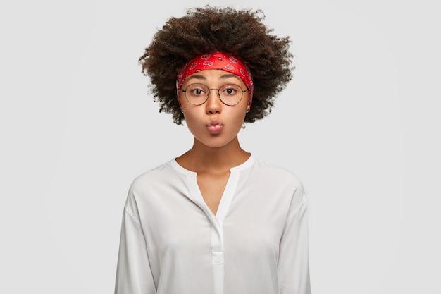 美しい暗い肌の女性は唇を吐き出し、アフロのヘアカットをし、しかめっ面をし、丸い眼鏡、赤いヘッドバンドと白いシャツを着て、壁に立っています。顔の表情の概念 無料写真