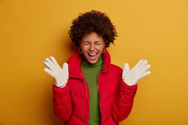 巻き毛の美しい暗い肌の女性は、冬のアウターウェア、白い手袋を着用し、幸せを表現し、喜びから叫び、黄色のスタジオの壁に隔離されています。 無料写真