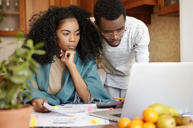 Bella giovane femmina dalla carnagione scura con acconciatura afro con sguardo preoccupato durante la gestione del bilancio familiare Foto Gratuite