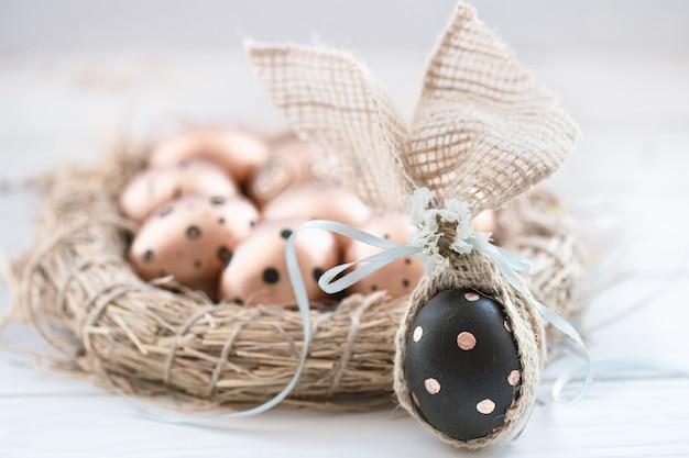 黒い点のある黄金色の美しい装飾イースターエッグと金色の点のある1つの黒い卵 無料写真