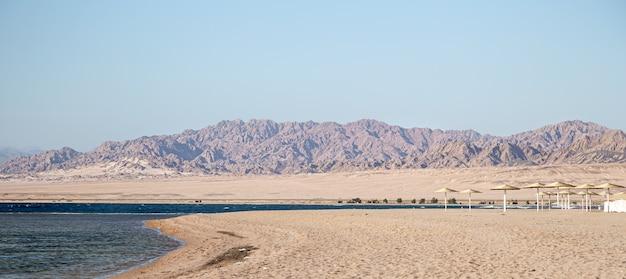 Bellissima spiaggia di sabbia deserta sullo sfondo delle montagne. turismo selvaggio e concetto di viaggio. Foto Gratuite
