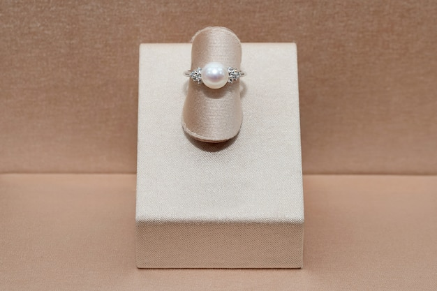 Beautiful diamond gold ring with shine sphere pearl displayed on a stand. luxury jewelry Premium Photo