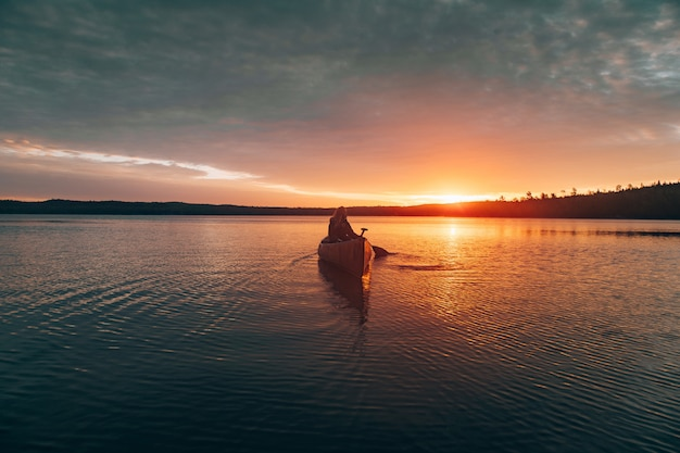 Beautiful distant shot of a woman riding  kayak in the middle of a lake during sunset Free Photo