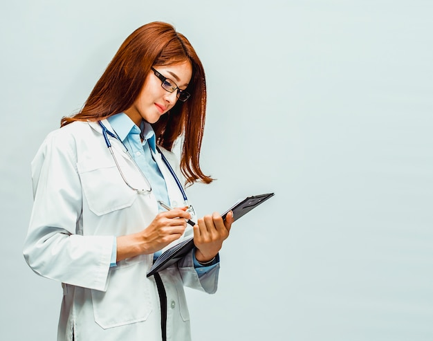 A beautiful doctor is writing a record of the patient's examination results Premium Photo