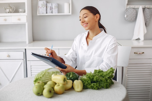 Beautiful doctor in a kitchen with vegetables Free Photo