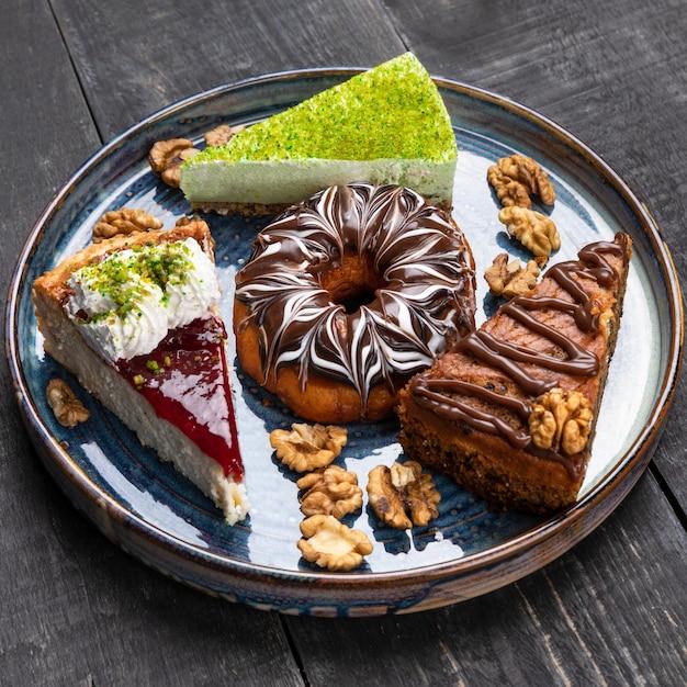 Красивый пончик, шоколадный торт, тирамису на синюю тарелку Premium Фотографии