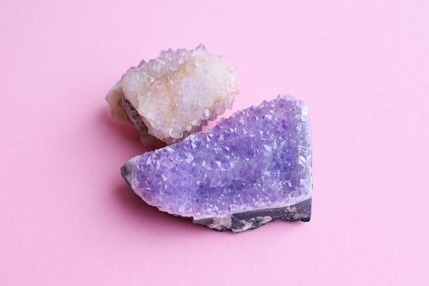 Красивая друза натурального фиолетового минерального аметиста и кристалла аметиста кактуса на розовой стене. крупные кристаллы драгоценных камней. Premium Фотографии