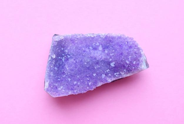 Красивая друза натурального фиолетового минерального аметиста на розовой стене. крупные кристаллы драгоценных камней. Premium Фотографии