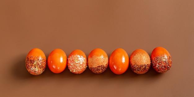 スパンコールでオレンジ色の装飾的な卵の美しいイースター。 無料写真