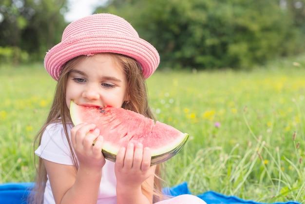 Красивые едят ломтик арбуза, сидя в парке Бесплатные Фотографии