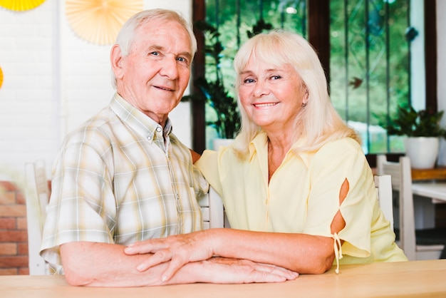 Beautiful elderly couple snuggling and looking at camera Free Photo