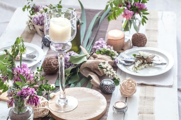 Красивый элегантно оформленный стол для праздника - свадьбы или дня святого валентина с современными столовыми приборами, бантом, бокалом, свечой и подарком Бесплатные Фотографии