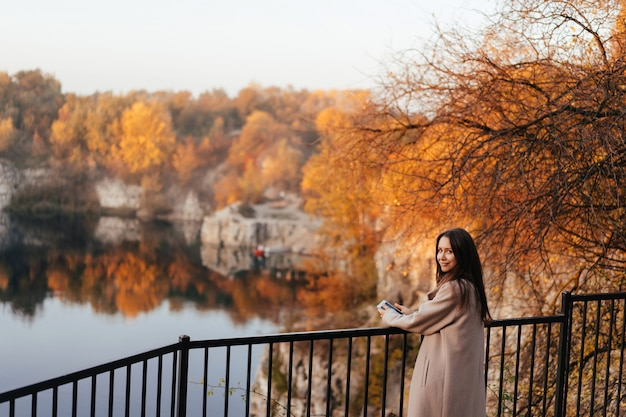 Beautiful elegant woman standing in a park in autumn Free Photo
