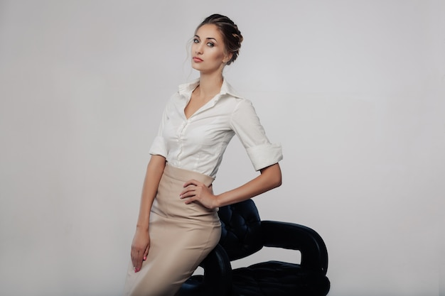 Beautiful elegant young bussines woman standing on the studio with gray background Premium Photo