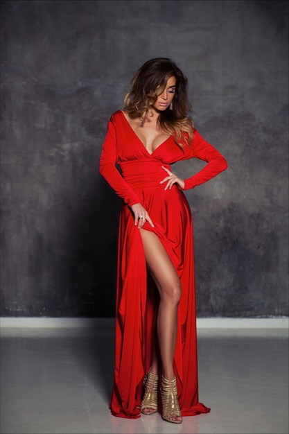 Beautiful elegant young woman with light brown hair, fashion make up and  hairstyle, posing in long red fitting evening dress and golden heels Premium Photo