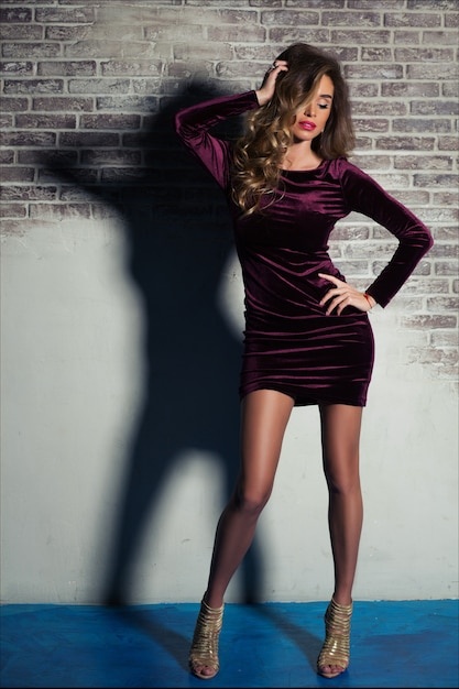 Beautiful elegant young woman with light brown hair posing in burgundy velvet  dress and golden heels Premium Photo