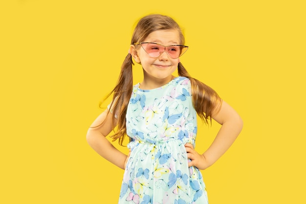 Beautiful emotional little girl isolated. portrait of happy child standing and wearing a dress and red sunglasses. concept of summer, human emotions, childhood. Free Photo