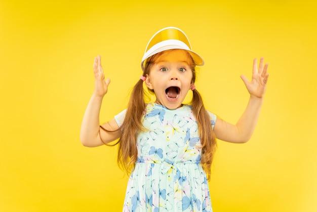 孤立した美しい感情的な少女。ドレスとオレンジ色の帽子を身に着けている幸せで驚いた子供の肖像画。夏のコンセプト、人間の感情、子供時代。 無料写真